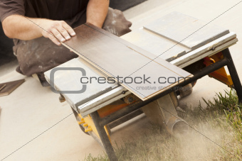 Contractor Using Circular Saw Cutting of New Laminate Flooring Renovation.