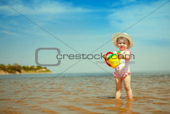 child with watering-pot on the seashore