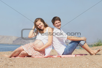 Happy young pregnant family at sea