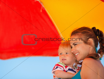 Happy mother and kid looking on copy space on beach