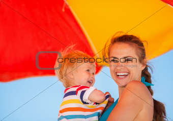 Portrait of happy mother and baby on beach under umbrella