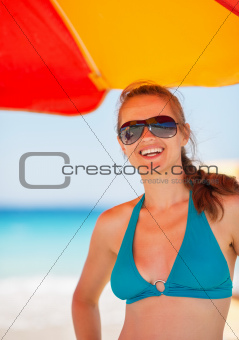 Portrait of smiling woman on beach under umbrella