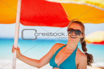Portrait of happy woman on beach under umbrella