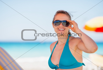 Portrait of smiling woman in sunglasses on beach