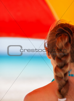 Woman on beach under umbrella looking into distance. Rear view