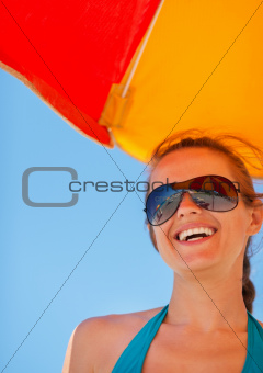 Portrait of smiling girl on beach under umbrella