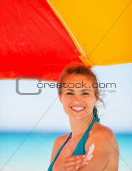 Smiling woman applying sun block creme on arm