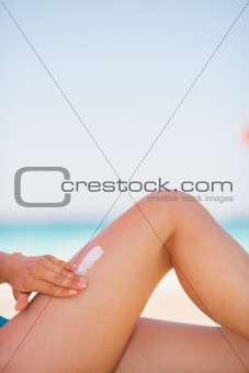 Closeup on female hand applying sun block creme on leg
