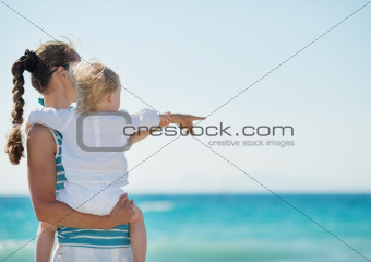 Mother and baby on beach pointing on copy space