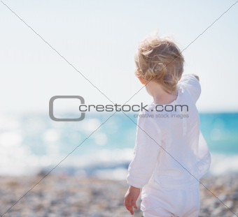 Baby on beach pointing into distance