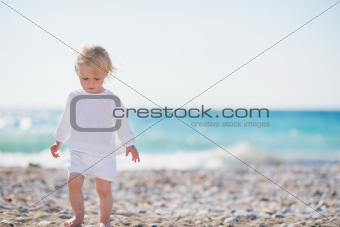 Baby walking on beach