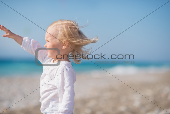 Baby on beach looking into distance