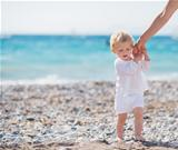 Baby holding mothers hand and walking on beach
