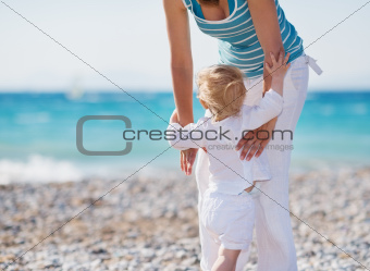 Baby on beach climbing mothers hands