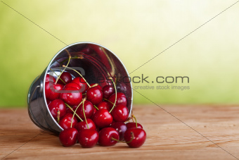 Cherries in a bucket on old wooden table