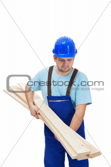 Worker in uniform carrying wooden planks