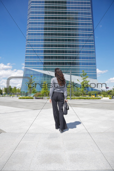 businesswoman walking to skyscraper