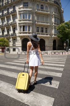 female walking with suitcase on crosswalk