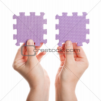 Hands holding foam puzzle pieces