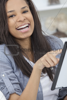 African American Woman Using Tablet Computer At Home