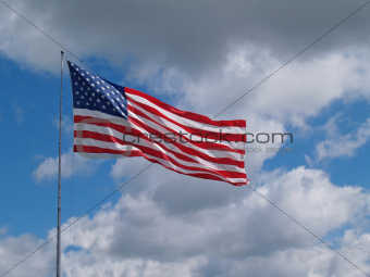 American Flag Flying in front of a Blue Cloudy sky