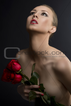 gilr's low key portrait with roses, she looks up