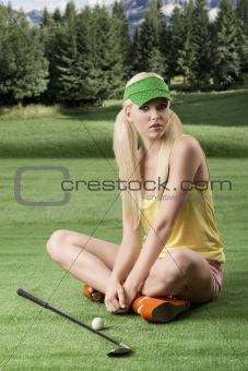 sexy golf player woman, she is sitting on the grass