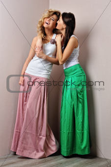 Two beautiful woman posing in a fancy dresses
