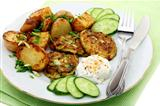 Fritters zucchini, potatoes and sour cream sauce.