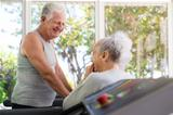 Active senior friends talking and working out in fitness club