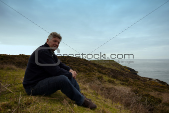 A mature  man sitting on the coastal path