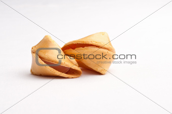 Two unbroken fortune cookies touching against faded white background
