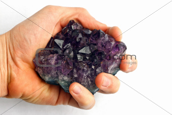 Purple amethyst crystal in hand against white background