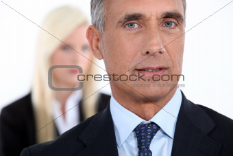 Male executive with female colleague out of focus in the background