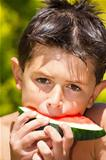 wet boy with watermelon in the garden