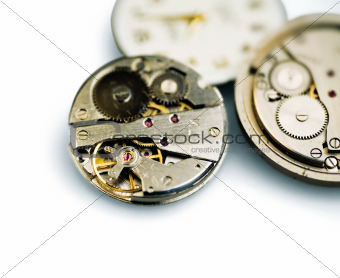 Old metal mechanical clock with gear wheels on a white background