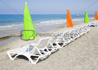 Beach chair and colorful umbrella on the beach