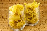 Two varieties of pasta inside two transparent glasses