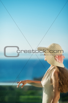 Woman looking on sea on balcony and relaxing