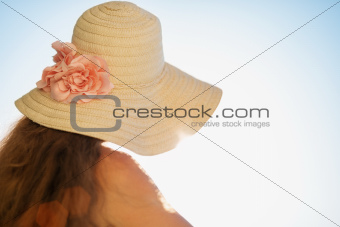 Woman looking on sea from balcony and enjoying sunshine