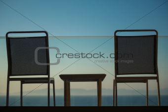 Sunset sea view from balcony with chairs and table