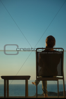 Woman enjoying sunset sitting on balcony. Rear view
