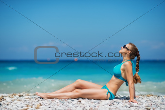 Woman in sunglasses enjoying sunshine on beach