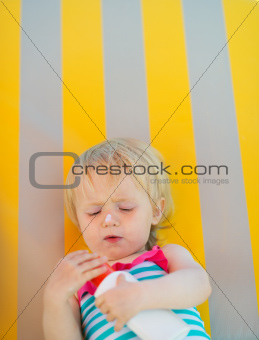 Baby laying on sunbed and using sun screen creme