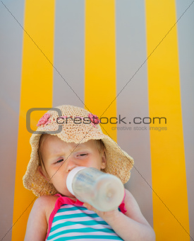 Baby laying on sun bed and drinking from bottle