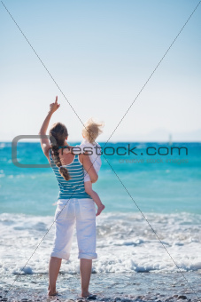 Mother and baby on sea coast pointing on copy space