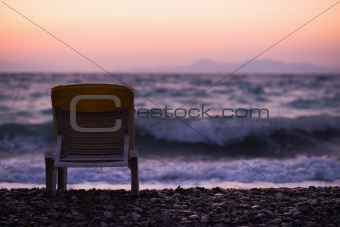 Lonely sea shore with sun bed in dusk