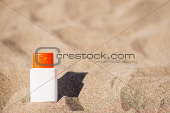 Bottle of sun block creme on sand