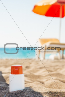 Bottle of sun block creme in shadow on beach