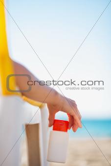 Closeup on bottle of sun block creme in female hand